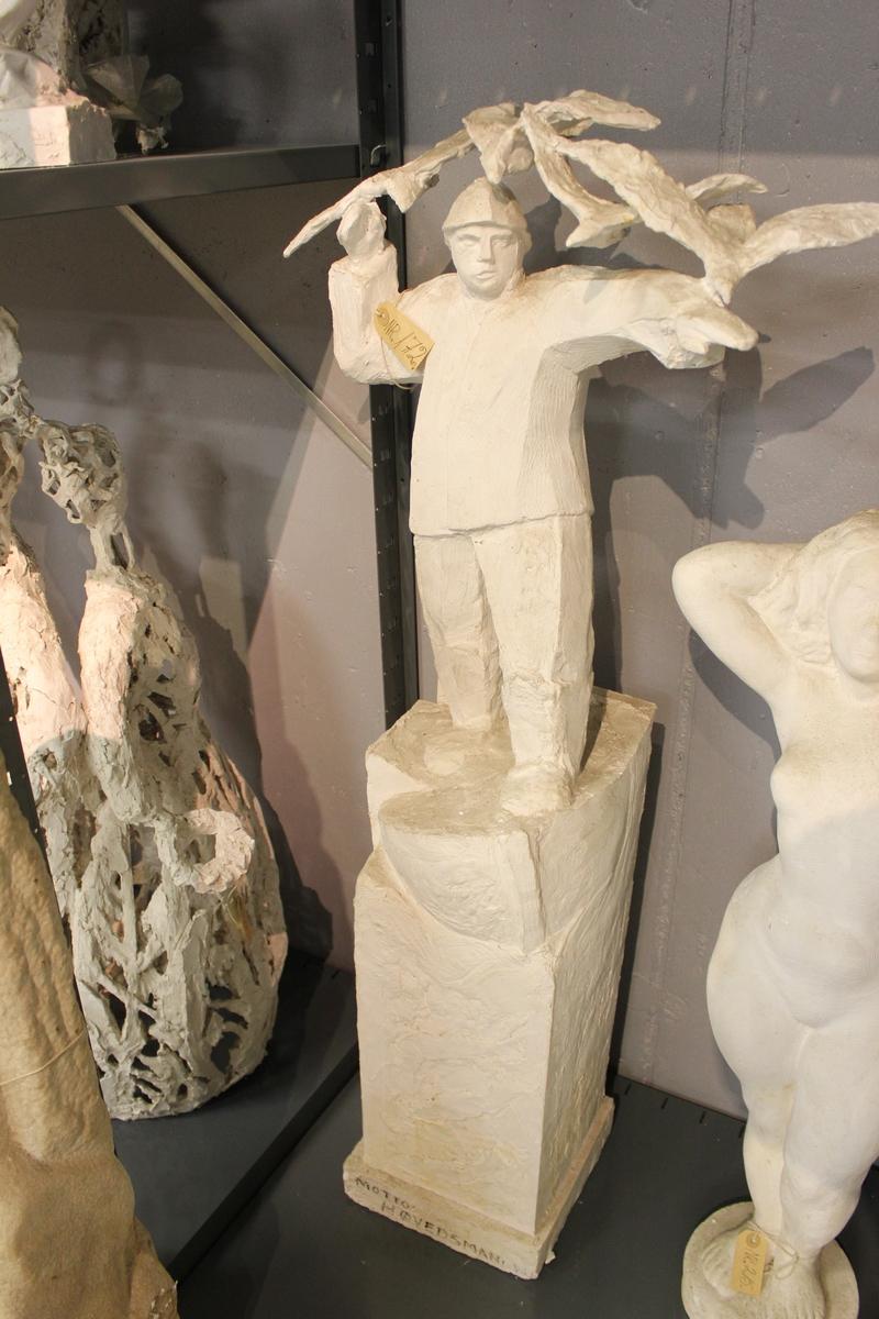 """Skulptur i gips på sokkel av en fisker som peker utover med måker som flyr over. Tittel: """"HØVEDSMANN"""". Konkurranse utkast til monument som står i Ålesund."""