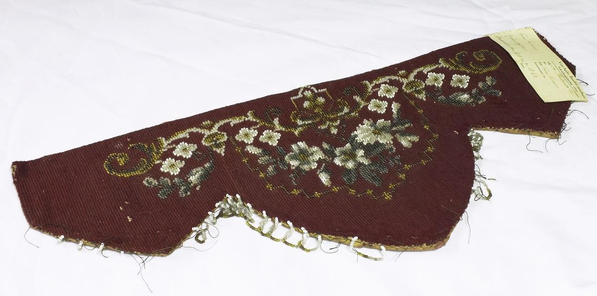 Rødt perlebroderi. Har merkelapp fra Vest-Agder Bondekvinnelags Tekstilregistrering 1953.