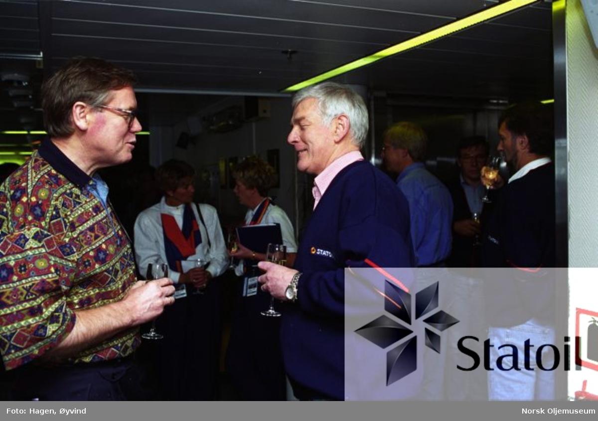 Et knippe gjester er samlet på Statfjord C i forbindelse med åpningen av Statfjord Satelitter.  Kommunalminister Gunnar Berge t.v. er her i samtale med en ukjent representant fra Statoil.