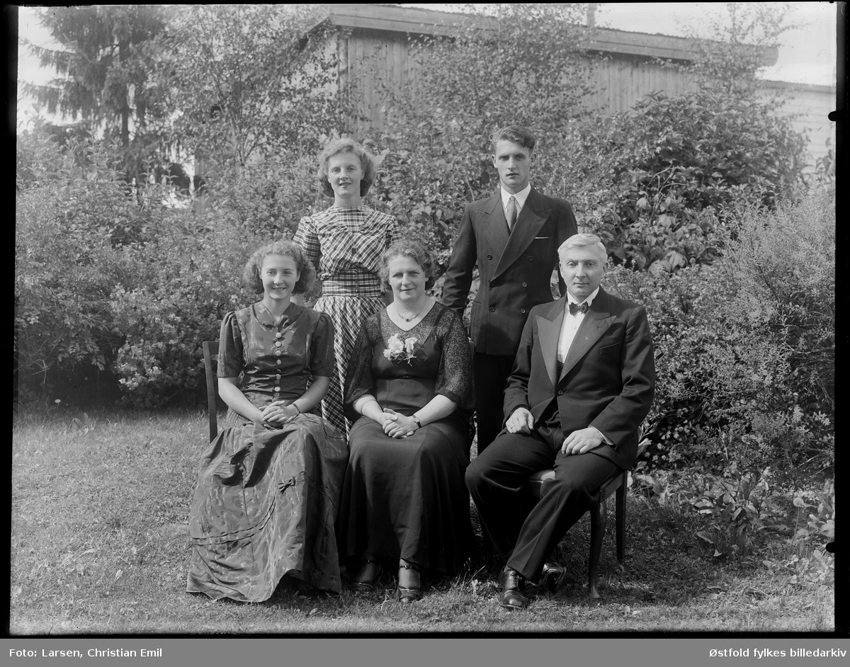 Pyntet ektepar med tre barn fotografert i hage,  Rakkestad? 1943. Ukjente persone.