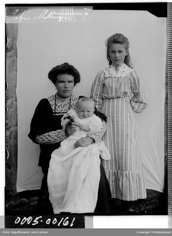 Gruppebilde av kvinne, jente og et spedbarn iført dåpskjole.