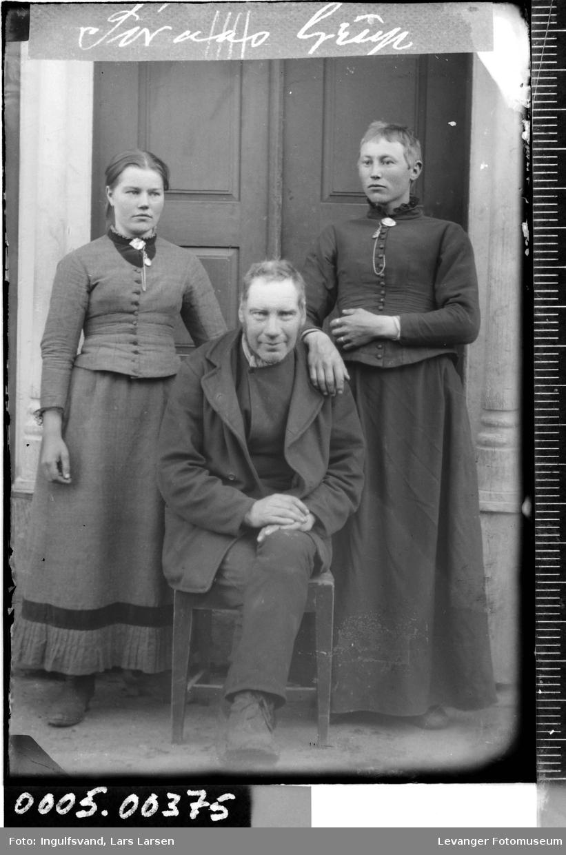 Gruppebilde av to kvinner og en mann foran et inngangsparti.