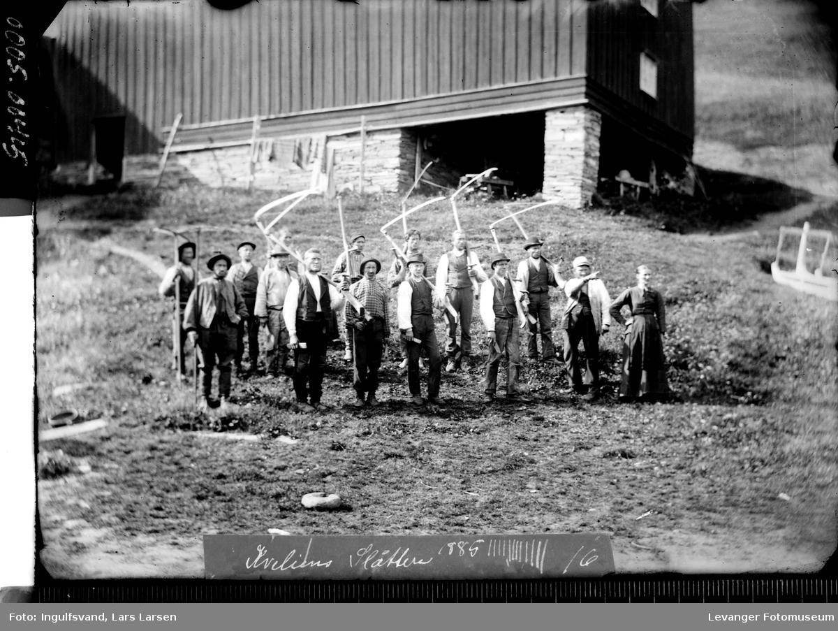 Gruppebilde av tretten menn og en kvinne foran et fjøs,mennene bærer ljåer, på veg til slåttonn.
