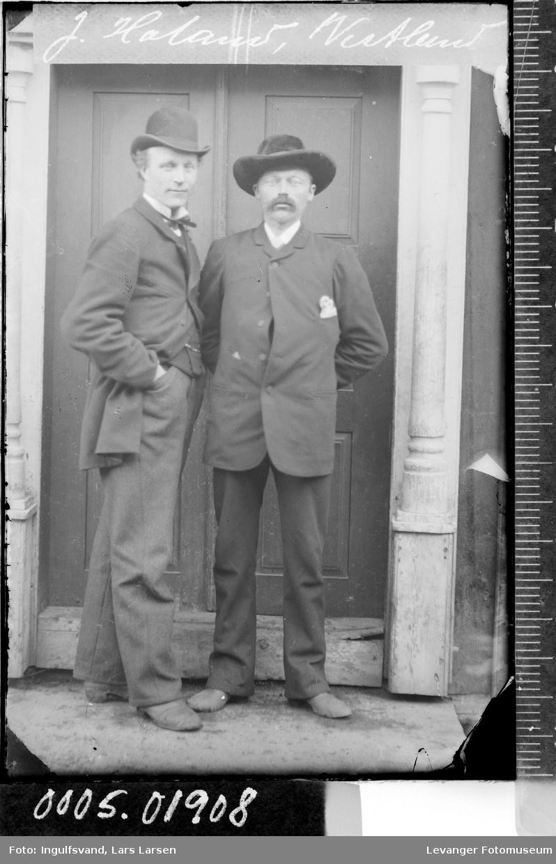 Portrett av to menn ved et inngangsparti.