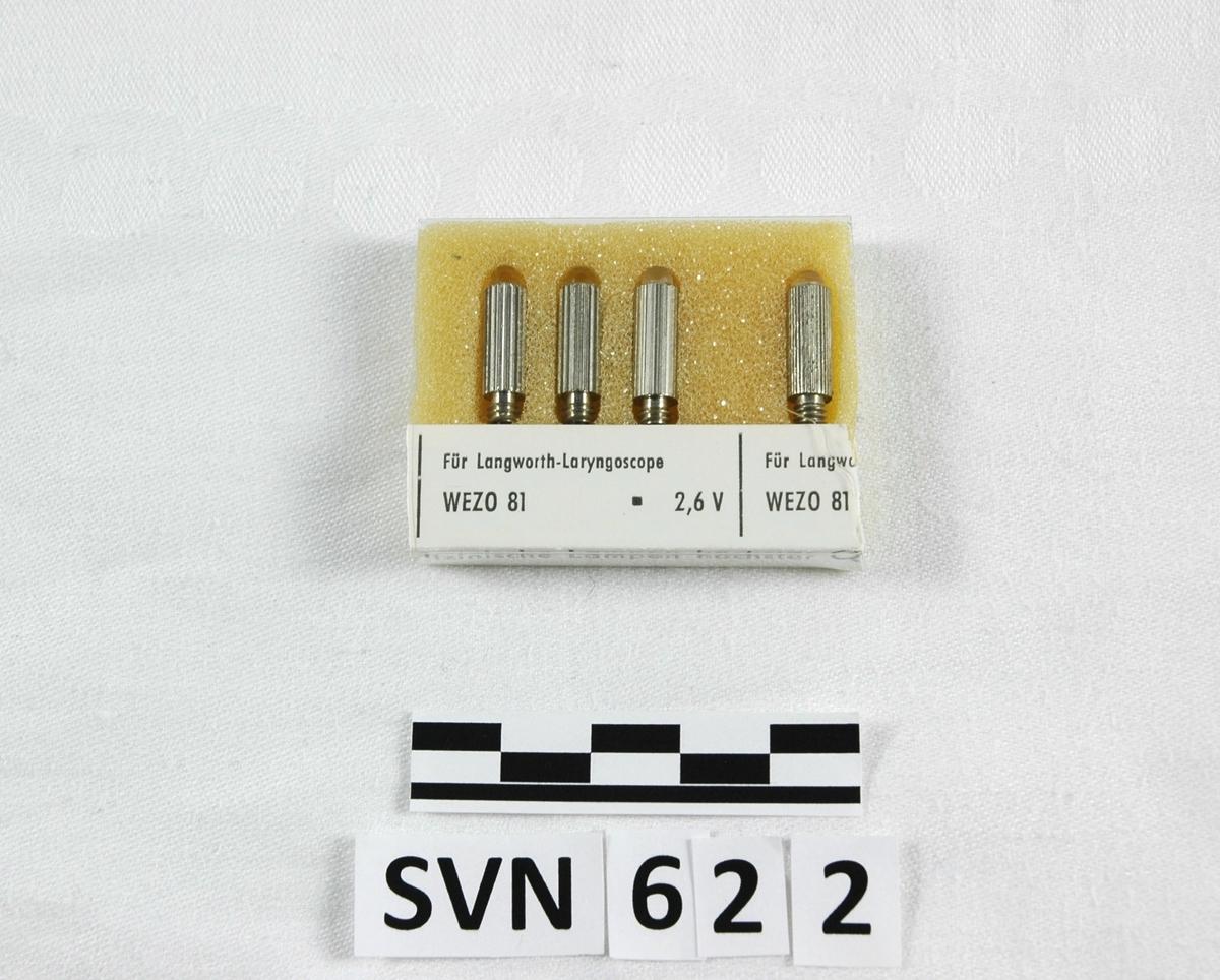 Pakke med fire små lyspærer til et instrument. Pærene har en avlang metallkropp med langsgående riller. Selve glasspærene er små. De er pakket inn i polyuretanskum(skumgummi), et pappomslag med tekst og et plastomslag ytterst. Pakken har vært større, men er kuttet av.