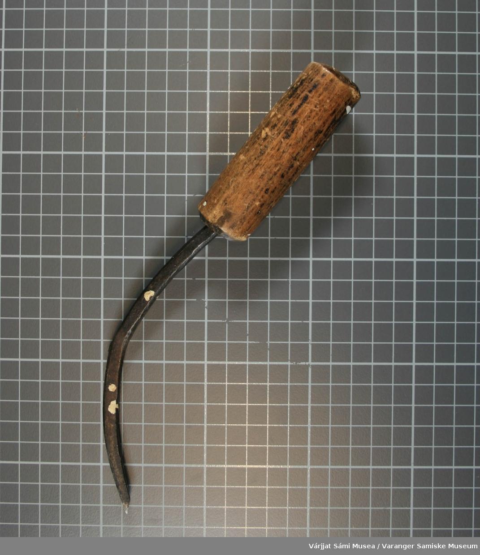 Trehandtak og blad av jern. Det er en sprekkdannelse i jernet. Redskapet har flekker av maling. Brukt til uthuling av tremateriale. Selvet jernet har en buet form.