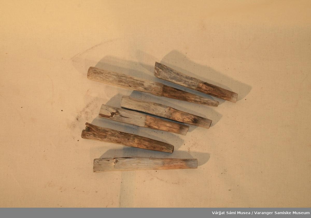 Seks tollepinner av tre. En lang og fem kortere. Litt bredere øverst, smalner nedover.
