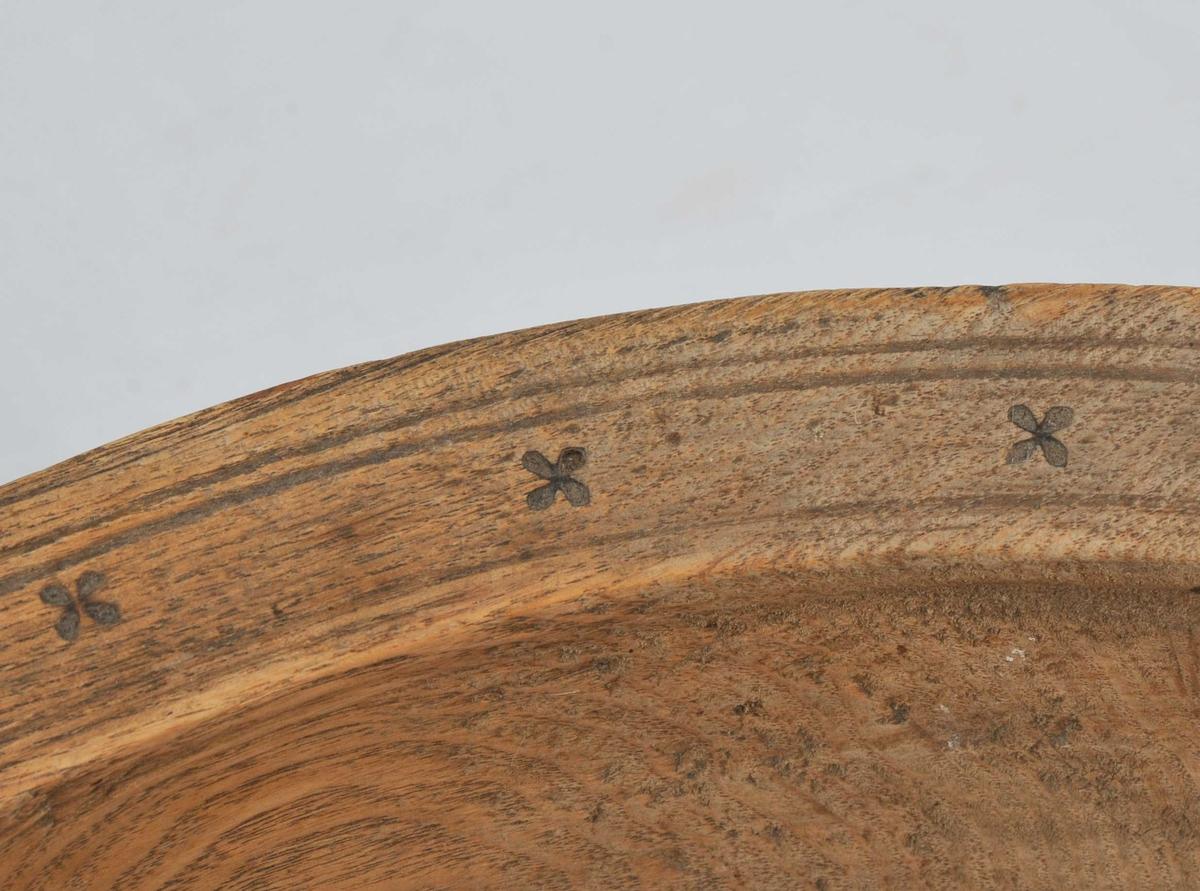 Dreia, stort fat med ein brei øvre kant. I denne er det svidd inn kors/blomar med riller over og under. Utvendig er det skore inn horisontale riller  frå øvre kant og ned til stetten. I botnen er det bruka sviteknikk til å svi inn prikka liner som endar i korsformer. Forma er ein stor V med to skråliner som går ut frå den eine sida i V-en. Kan vere bumerke. Bollen har ein stor sprekk tvers over den eine sida.