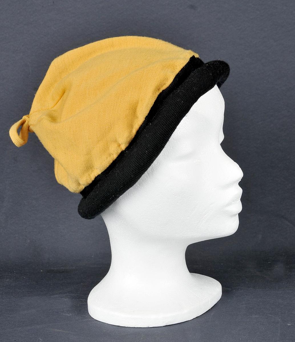 Hatt i luefasong.  Pullen er av einsfarga gul ulltrikot med sløyfe i toppen. Neders svart, opprulla kant av same type stoff.