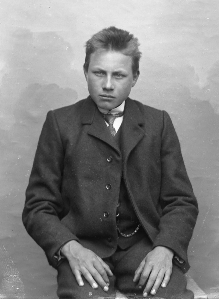 Sittende ung mann foran hvitt lerret