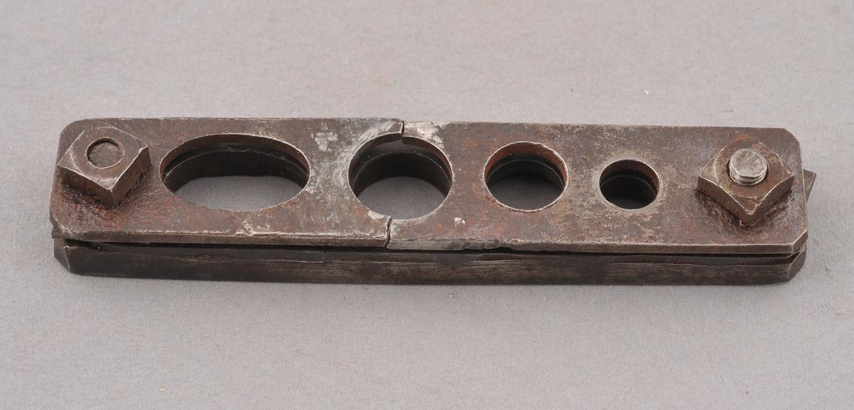 Lo av to metallplater som er festa saman i kvar ende med ein skruve tvers gjennom.  Det er stansa ut fire hol parallelt gjennom begge plater.