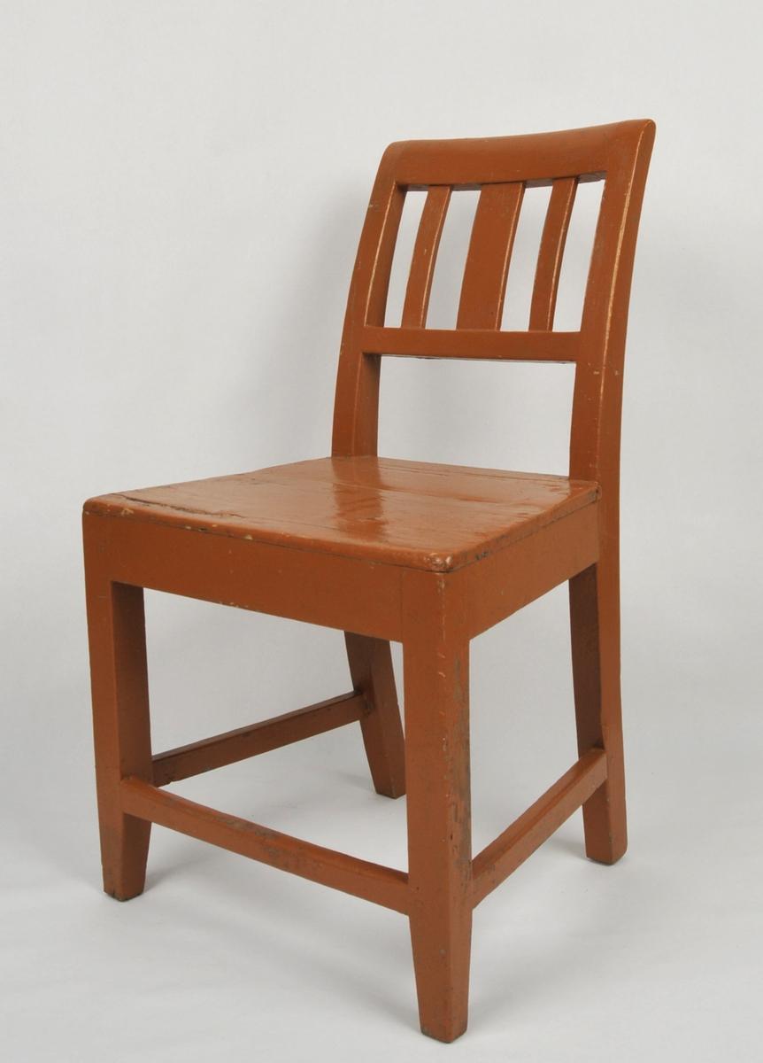 Grindestol med gul måling. Ein horisontal og tre vertikale spiler i ryggen. Fire bein med tverrspile på kvar side og i front. Sprekkar i sete.