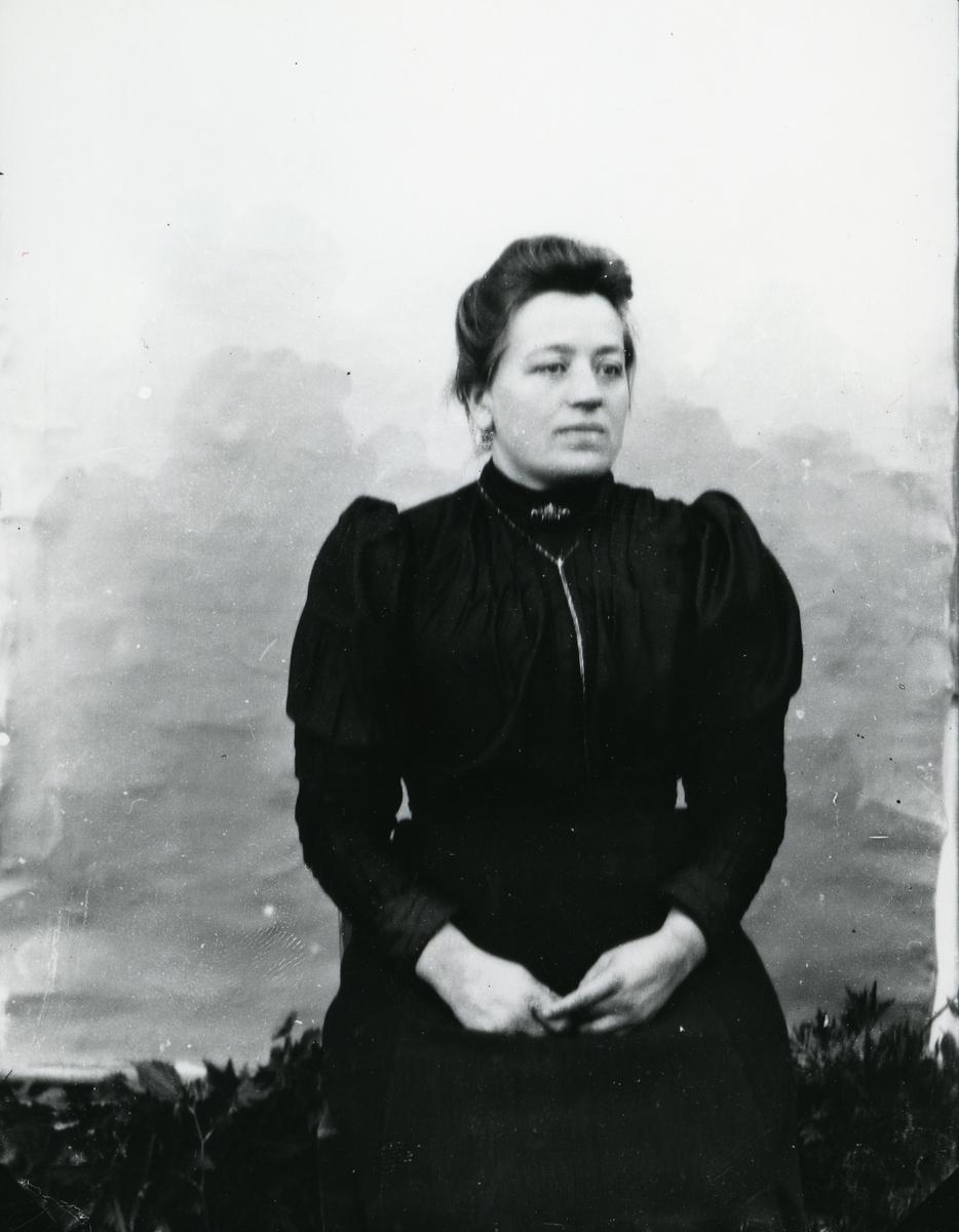 Kvinne i halvfigur, sittende, kledd i mørk kjole, lerretbakgrunn