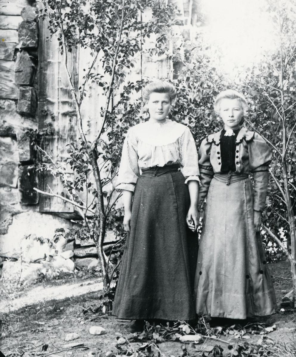 To kvinner i helfigur som holder hverandre i hendene. Stående foran bjørkekvister og tømmervegg