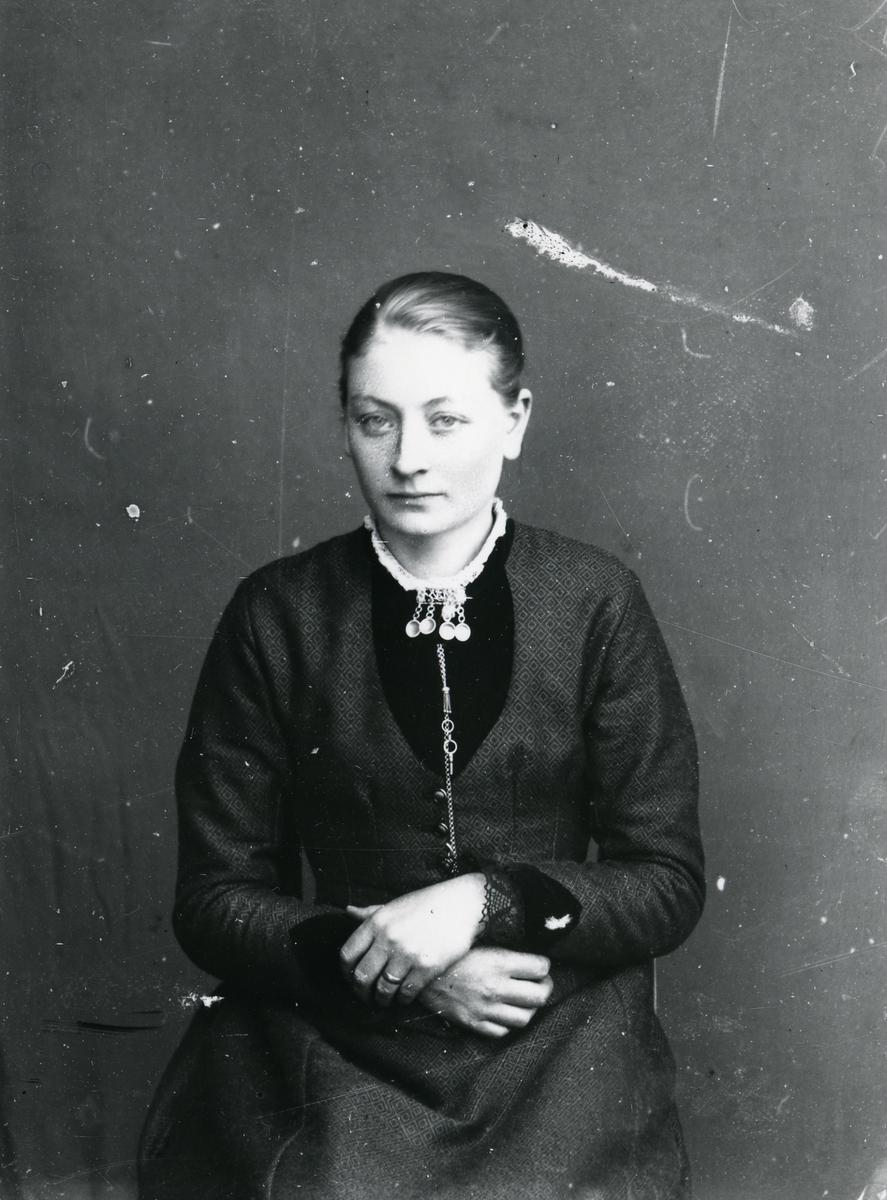 Kvinne kledd i mørk kjole, i halvfigur, sittende foran lerret