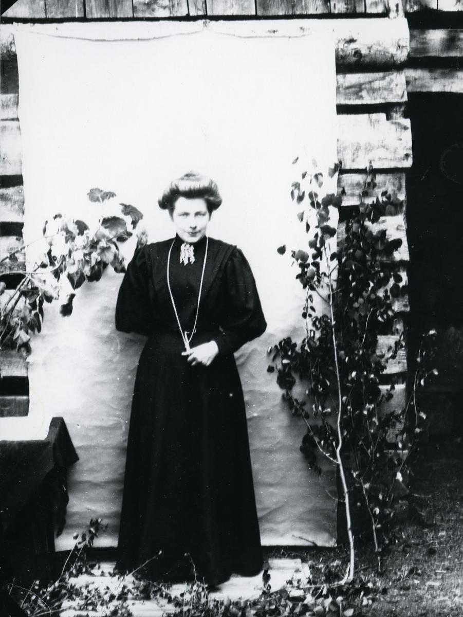 Kvinne kledd i mørk kjole med sølje, lerret på husvegg