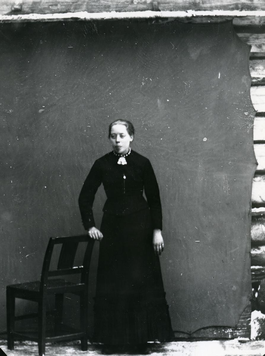 Kvinne i helfigur, stående ved stol foran lerret
