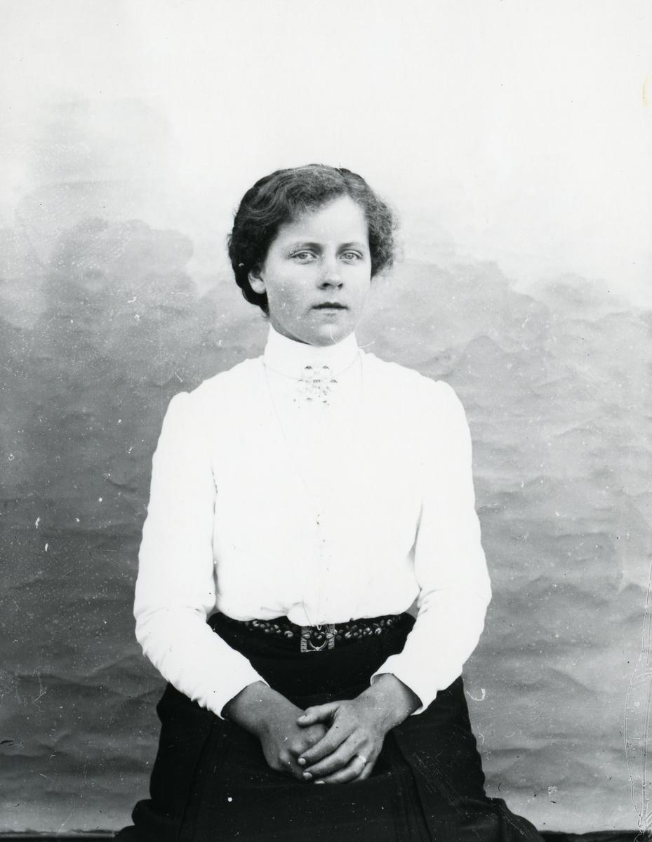 Kvinne i lys bluse, sittende foran lerret
