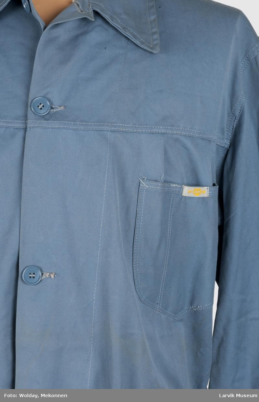 Form: Åpen foran med knapper, og belte, krage og tre lommer.