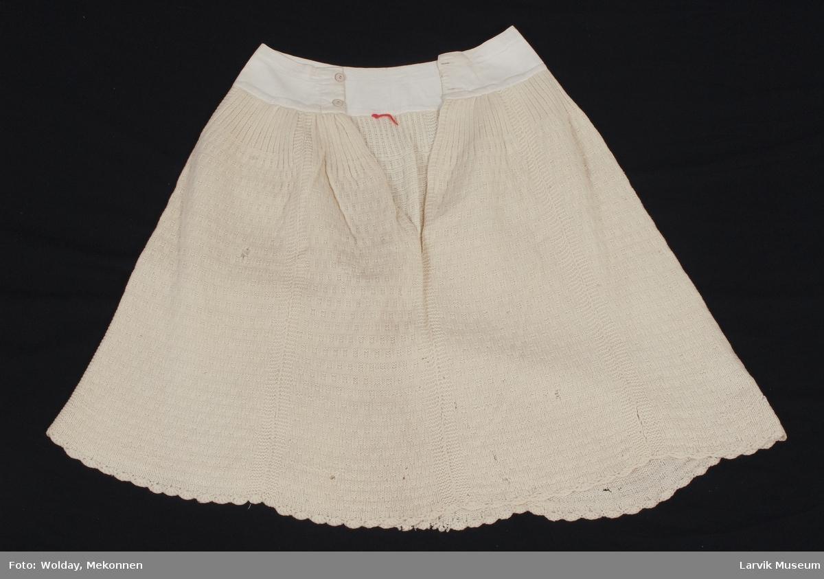 Form: Knekort lett utskrådd. Påsydd linning i stoff med knapping. Strikket rutemønster. Heklet tungekant i nedkant. Skjørtet består av 7 stykker som er sydd sammen.