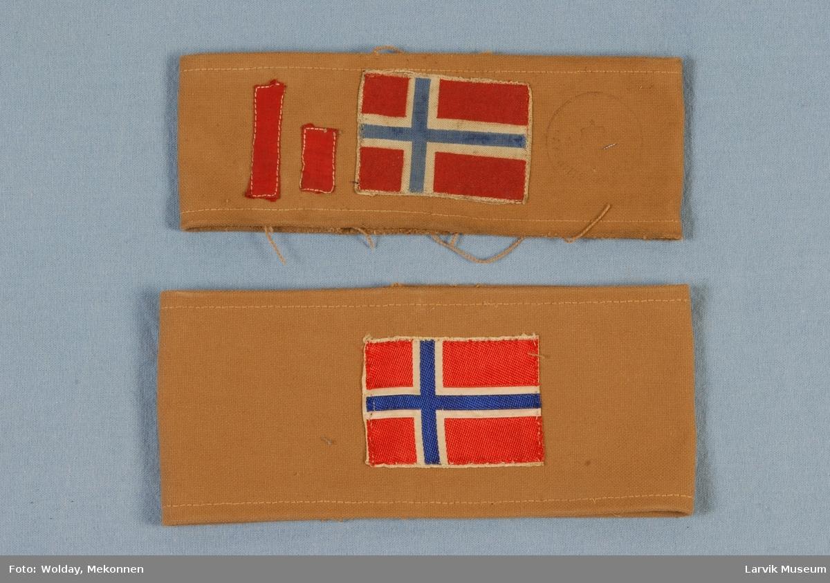 Form: Et sammensydd bånd av grovt stoff. Påsydd flagg og den ene påsydd bånd vertkalt.
