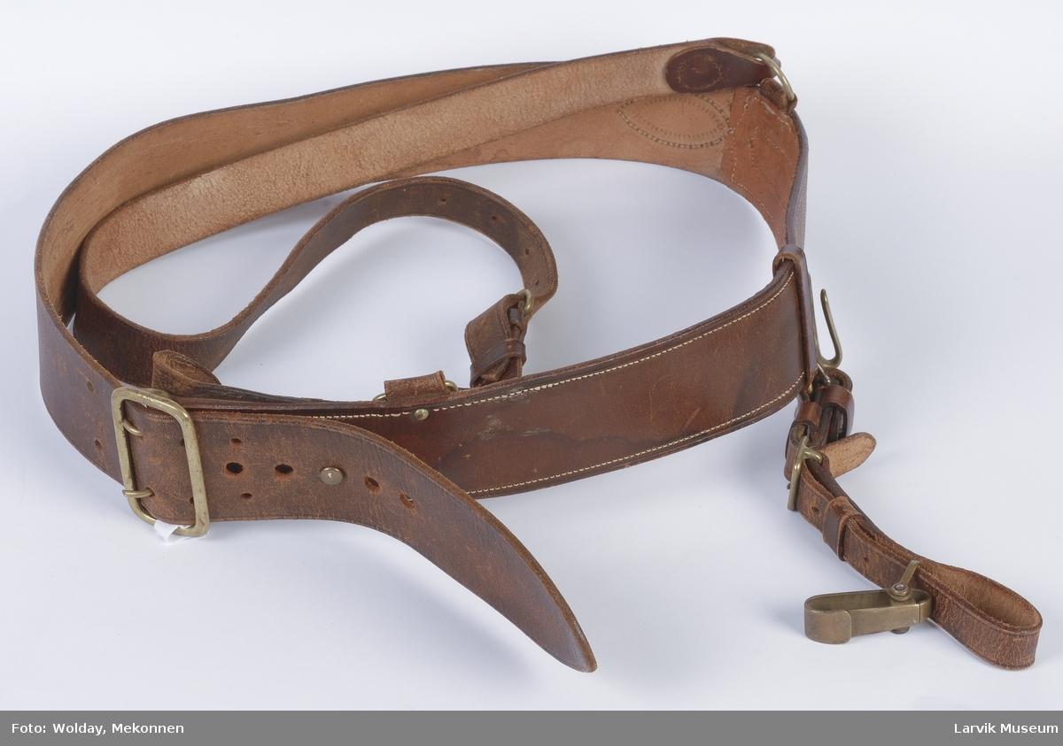 Form: Bredt belte med spenne for feste. Et smalere belte som går over skulderen.  Det brede beltet har en krok, og en stropp som henger ned.