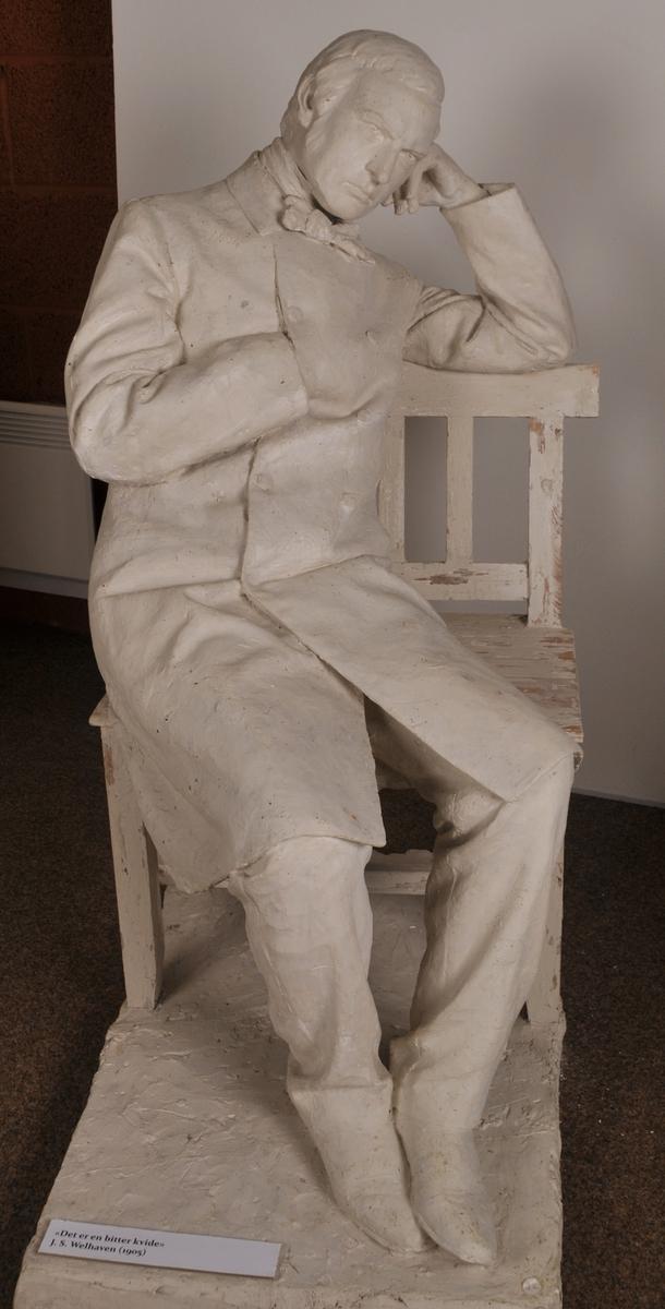 """Heilfigur av diktaren J. S. Welhaven, sitjande på ein benk. Motto frå verset """"det er en bitter kvide""""."""