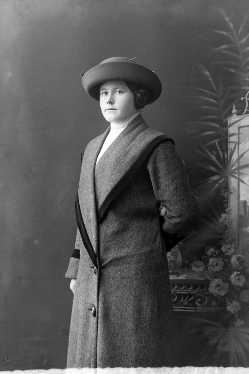 Studioportrett av en kvinne med hatt på hodet.