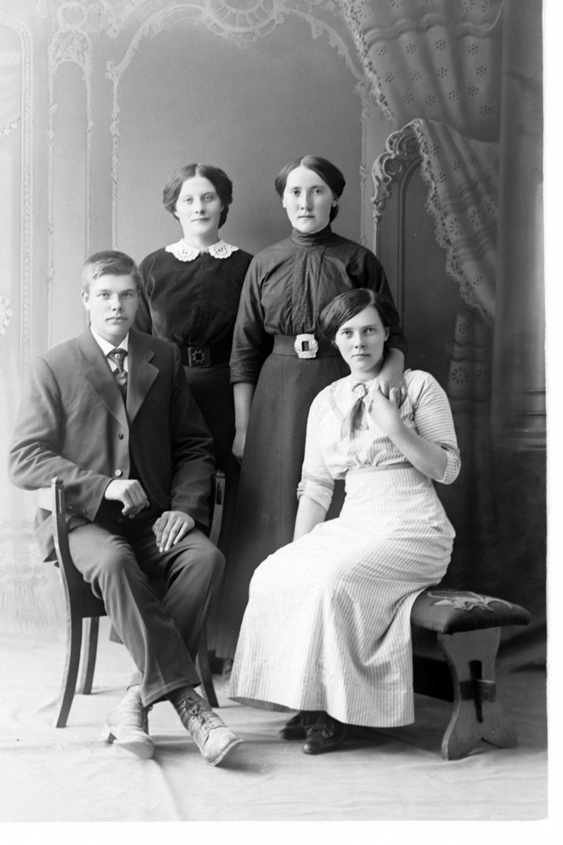 Studioportrett av tre kvinner med en mann i helfigur.