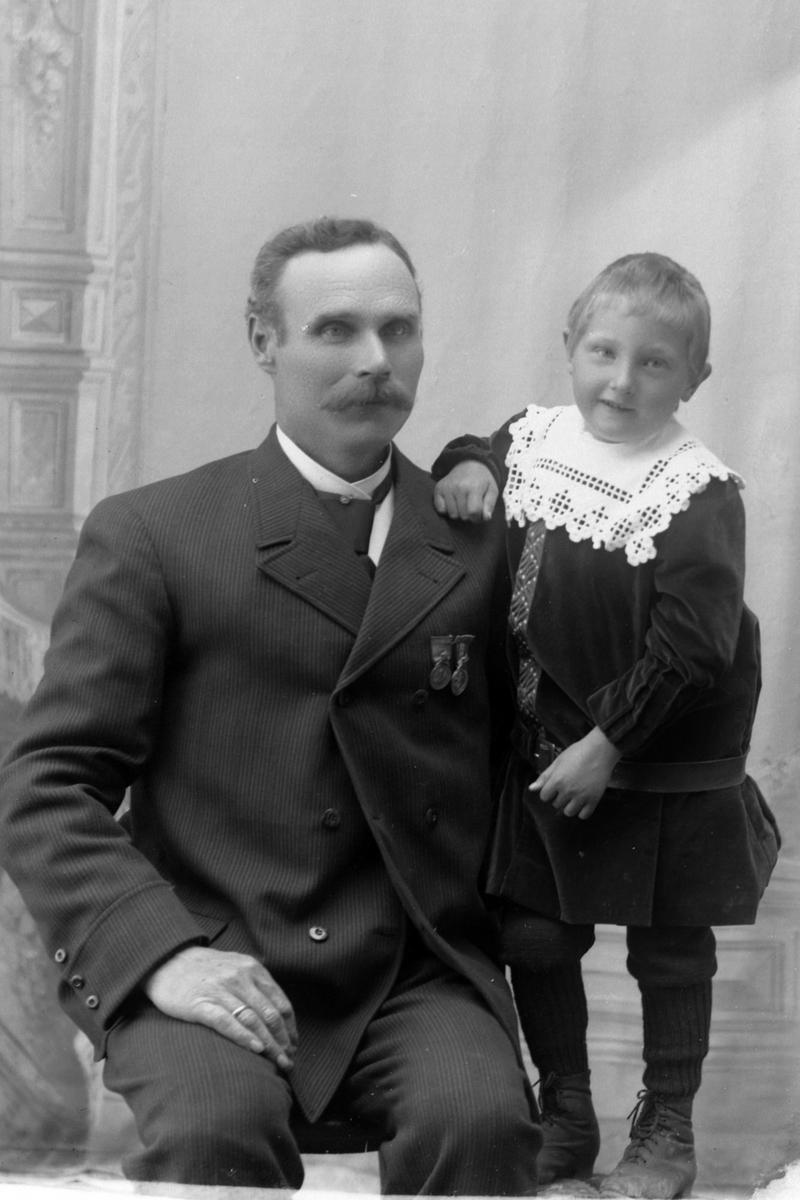 Studioportrett av en sittende mann med et barn ved siden av seg.