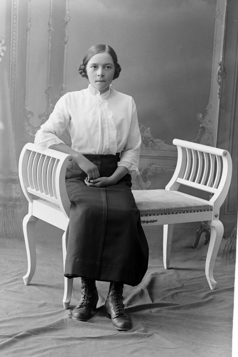 Studioportrett av en kvinne som sitter på en benk.