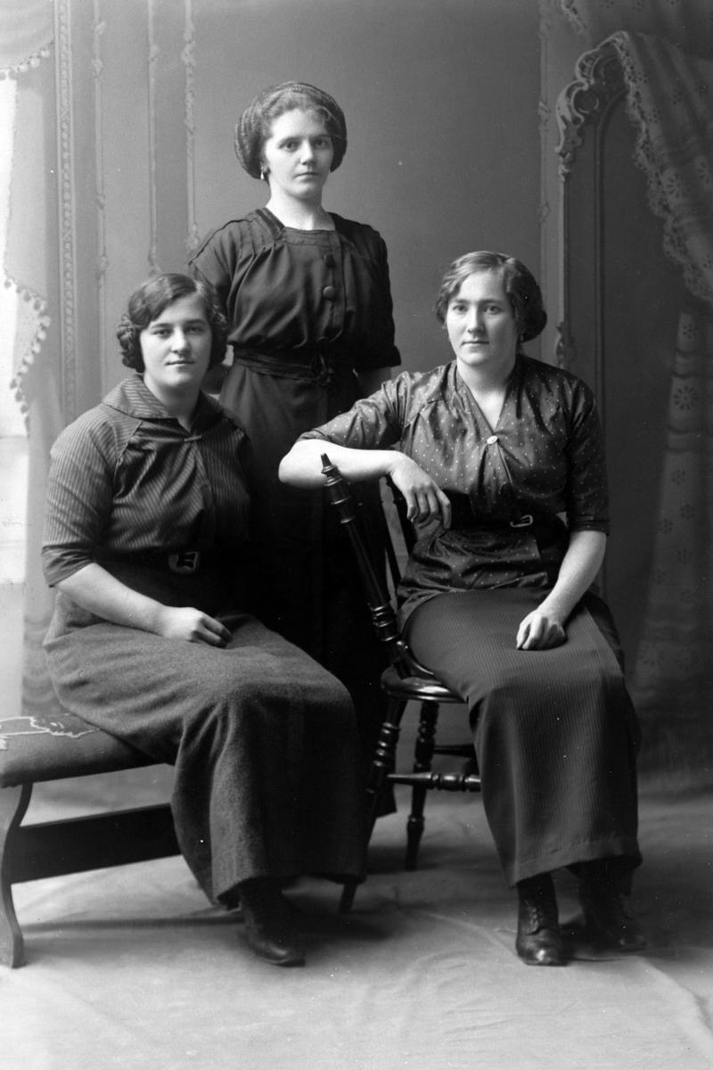 Studioportrett av tre kvinner i helfigur.