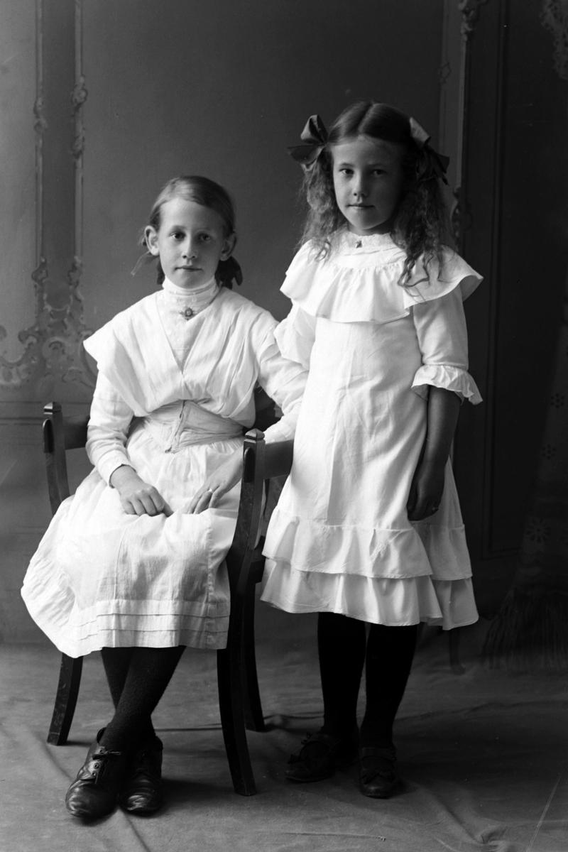 Studioportrett av to unge jenter i lyse kjoler.
