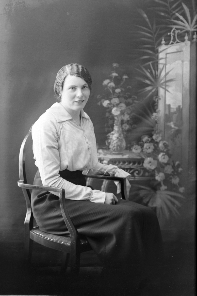 Studioportrett av en kvinne sittende i en stol.