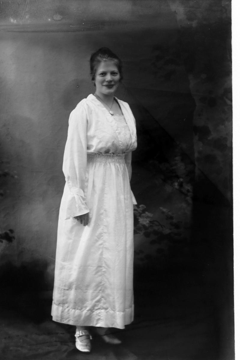 Studioportrett i helfigur av en kvinne i hvit kjole.