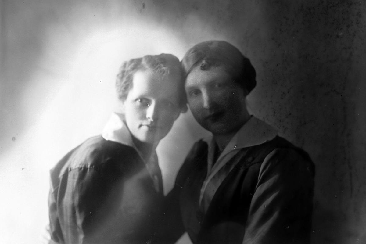 Studioportrett i halvfigur av to kvinner.