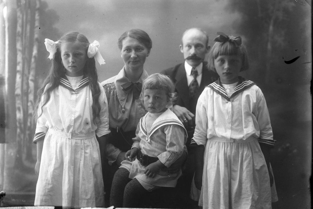 Studioportrett av en mann og kvinne med tre barn kledd i matrosdress.
