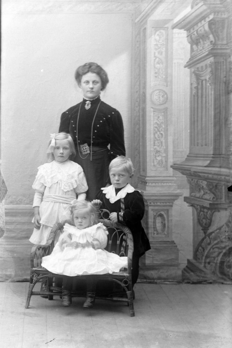 Studioportrett av en kvinne som står bak tre barn.