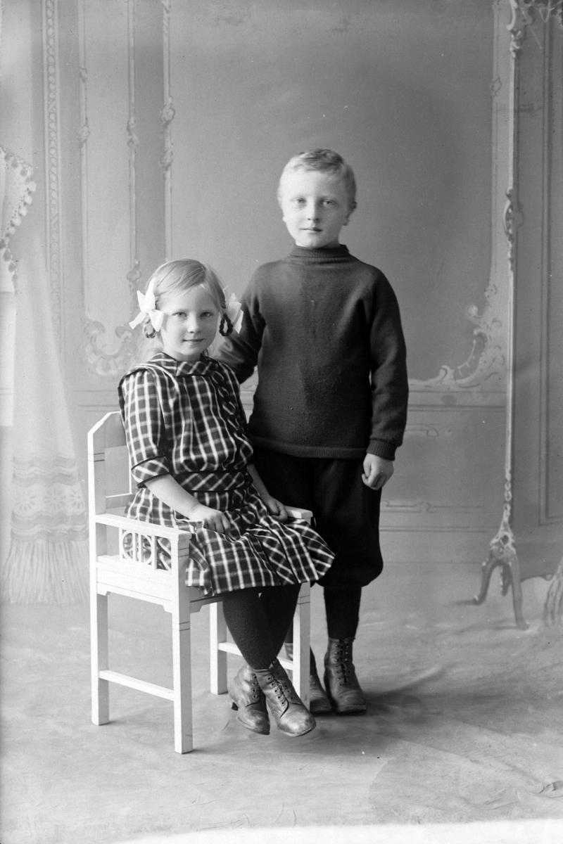 Studioportrett av to barn i helfigur.
