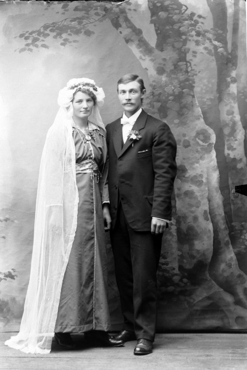 Studioportrett av et brudepar i helfigur.