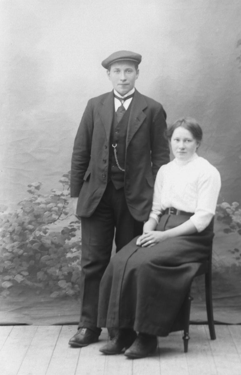 Studioportrett i helfigur av en mann og en kvinne.
