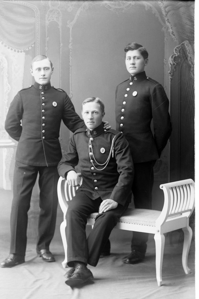 Studioportrett av tre menn i uniform.