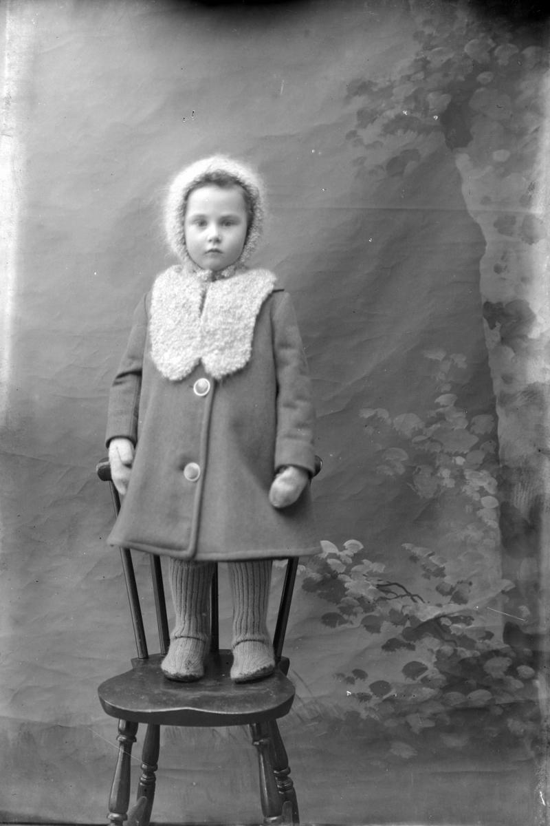 Studioportrett av en liten jente med lue og kåpe.