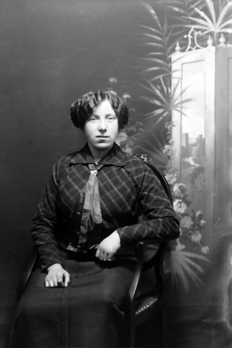 Studioportrett av en kvinne som sitter.