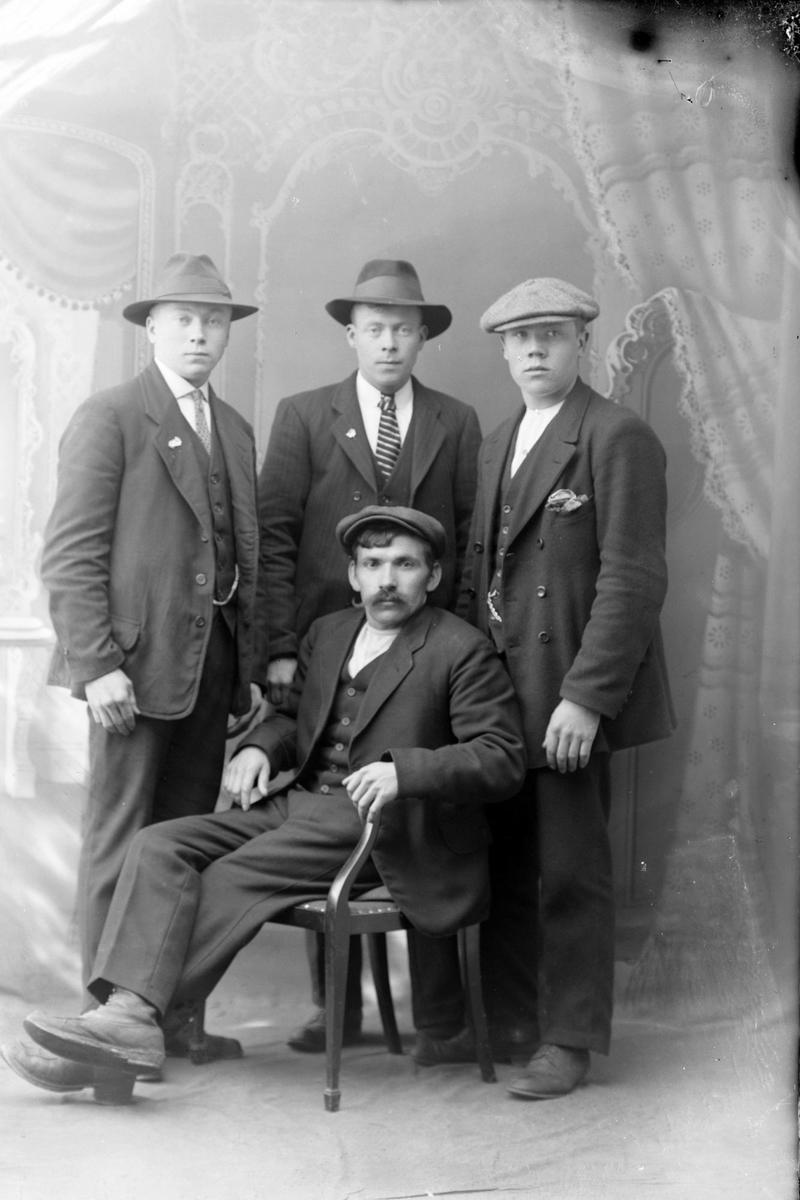 Studioportrett av tre menn stående bak én som sitter.