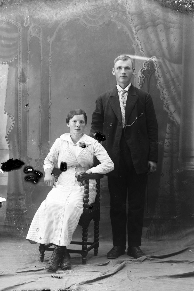 Studioportrett av en kvinne sittende ved en mann som står.