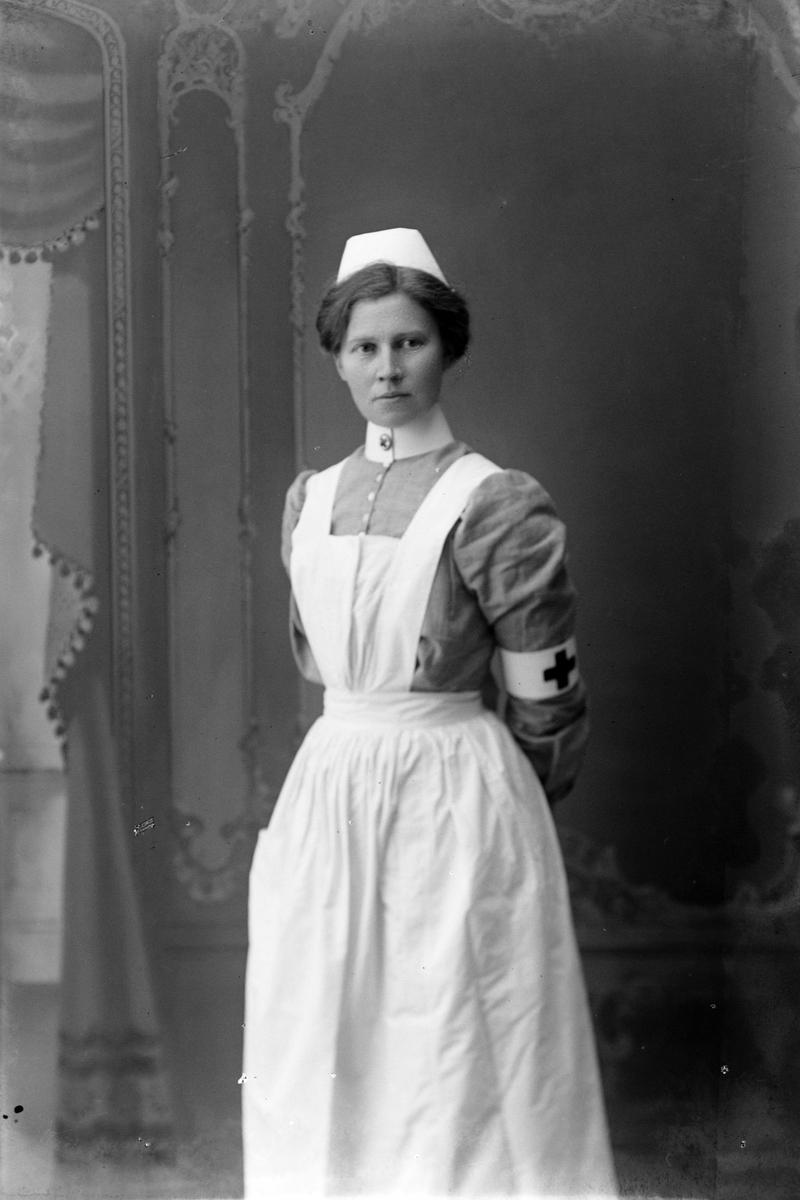 Studioportrett av en sykesøster i uniform.