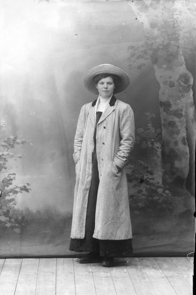 Studioportrett av en kvinne i kåpe.