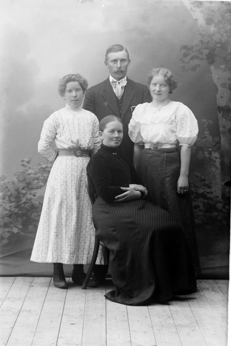 Studioportrett av en mann omgitt av tre kvinner.