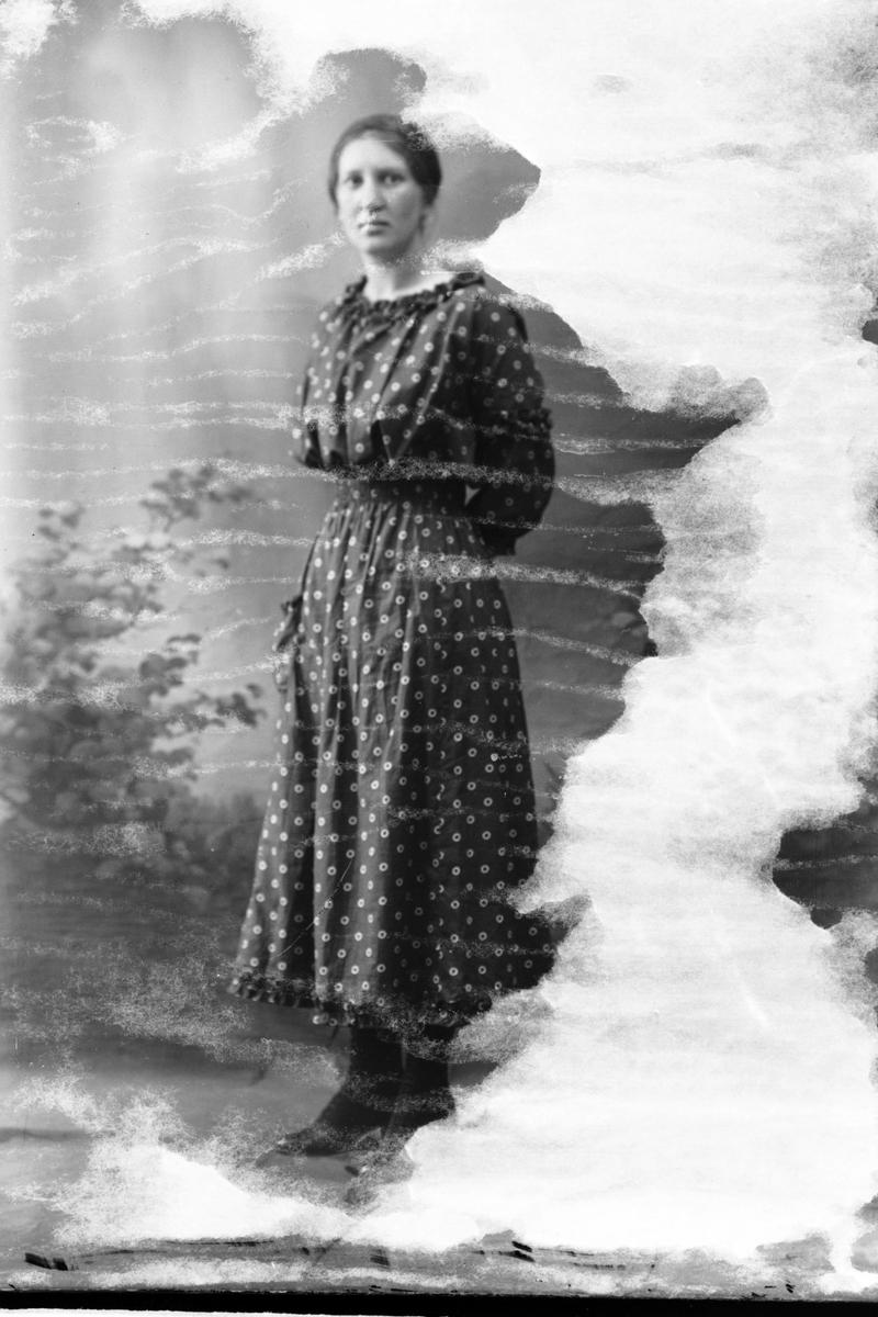 Studioportrett av en kvinne kledd i en prikket kjole.